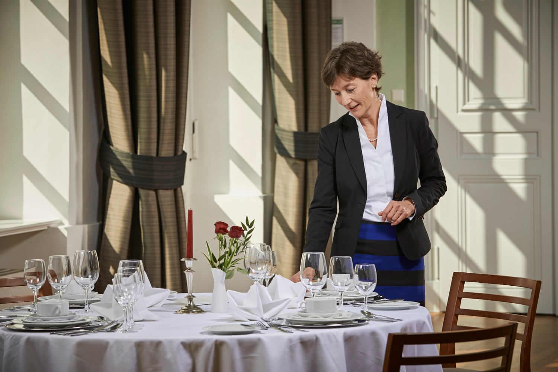 Business Knigge Coach Barbara Danowski steht am hübsch gedeckten Tisch und zupft einen Teller gerade