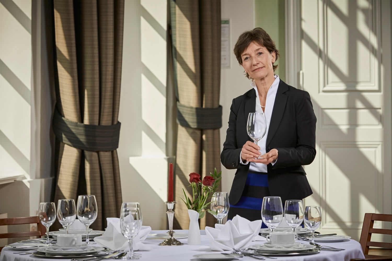 Business Etikette Coach Barbara Danowski steht vor einem schön gedeckten Tisch und präsentiert freundlich die Haltung eines Glases