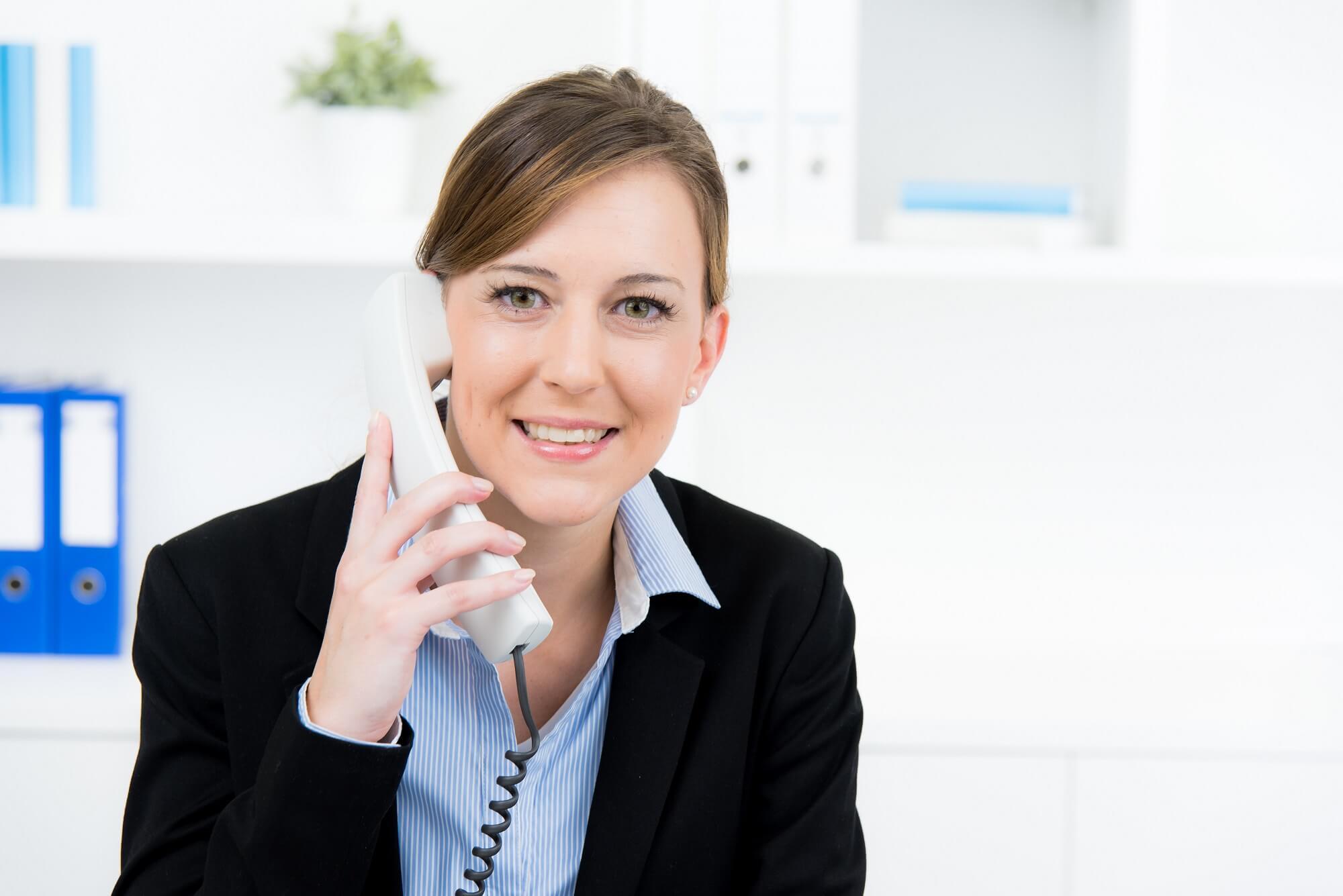 Eine freundliche Frau hat einen Telefonhörer in der Hand und telefoniert