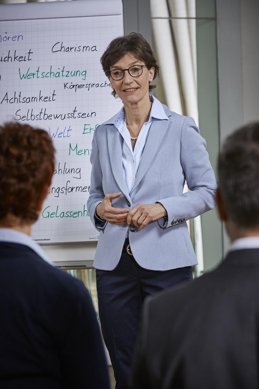 Der Business Knigge Coach Barbara Danowski steht vor einer Tafel und fragt die Zuhörer zu Umgang der Kunden beim Verkaufen