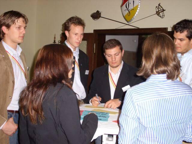 Verbindungsstudenten stehen um einen Tisch herum und arbeiten konzentriert zusammen
